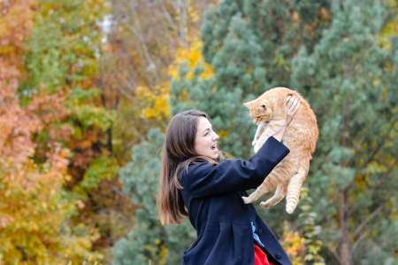 Happy young woman holding her red cat in park on autumn day