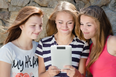 Three happy teen girl friends and tablet computer and laughing photo