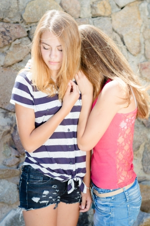 Two teenage girls hug for comfort on summer day at stone wall photo