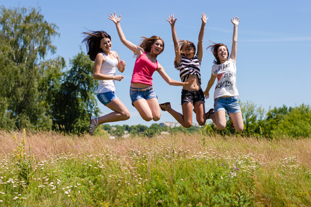 Four happy teen girls friends jumping high against blue sky photo
