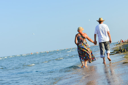 Happy mature couple walking at seashore on sandy beach and embracing photo