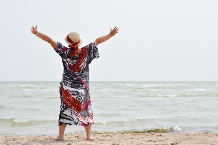 Happy mature woman in hat and sunglasses enjoying breeze on seashore