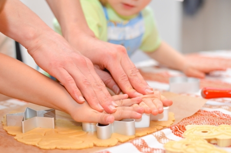 gi: Close up little hands making the gingerbread cookies with mother help Stock Photo