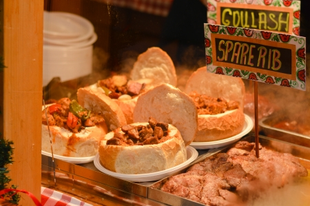 Goulash soup with beef, potato and meat sausage, served in a bread bowl on traditional Budapest food market photo