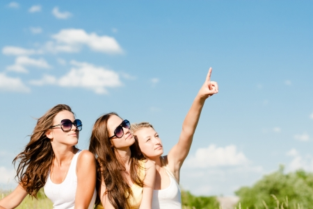 Three happy teen girls showing up into blue sky copy space sitting on green lawn photo