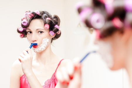 Young beautiful pinup woman shaving mustache with razor and foam