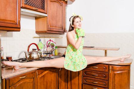 split lip: Beautiful pinup woman doing splits in kitchen