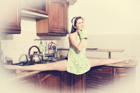 Beautiful pinup woman doing splits in kitchen photo