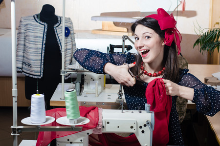 Funny young pinup woman with sewing machine and scissors photo
