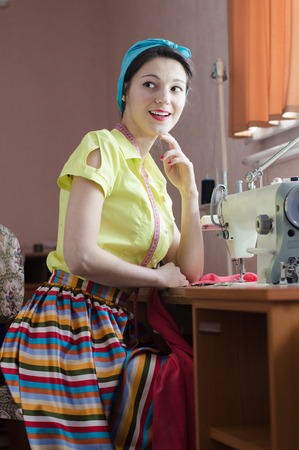 Funny young pinup woman with sewing machine and measuring tape photo