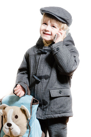boy or kid talking on mobile phone happy smiling & looking at camera photo