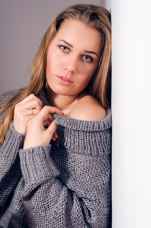 beautiful blond young woman looking at camera in knitwear photo