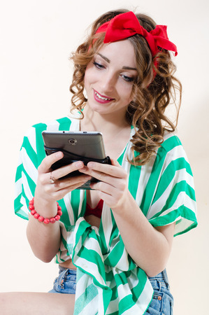Beautiful pinup woman holding tablet pc computer & happy smiling over white background photo