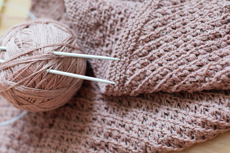 Detail of woven handicraft knit woolen design texture and clew. Fabric pink background