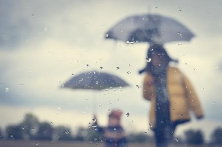 sotto la pioggia: Madre e figlio sotto l'ombrello silhouette attraverso la finestra bagnata