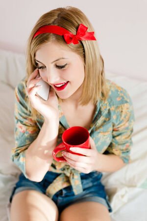 holding cup of hot drink & mobile cell phone beautiful blonde pinup young woman girl with red lipstick photo