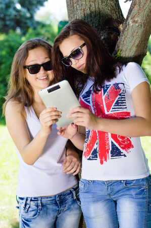 studens: Two young teenage girs studens sitting in park with tablet pc