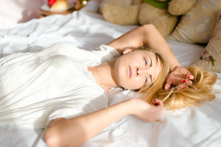 bedstead: attractive sincere young blond woman tender girl lying in bed in the sunlight