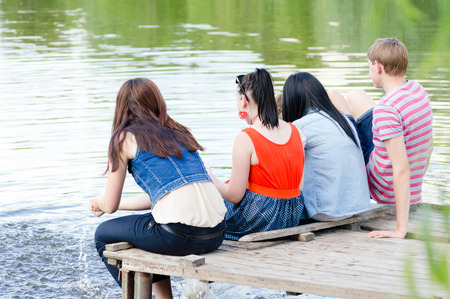 sociable: Young teenage friends people happy hugs   sitting on the bridge at the river on summer water lake outdoors background