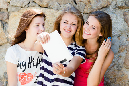 Three young women girl friends with different hair happy laughing at tablet blogging message photo