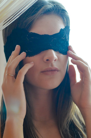 One beautiful glamour young woman with black band of lace on the face blindfold photo
