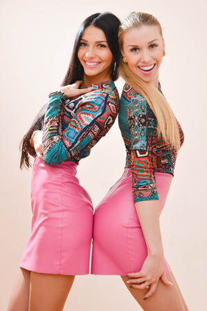 Two young beautiful women blonde & brunette with long hair & identical costumes happy smiling & looking at camera Stock Photo