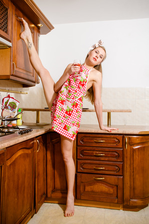 houseclean: super stretched leg-split flexible beautiful young woman pinup blond girl with a lovely body drinking beverage in the kitchen