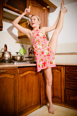 Young athletic, flexible, pin-up woman blonde girl at the stove tastes soup with scoop or ladle Stock Photo