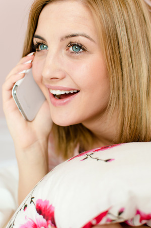 portrait of beautiful happy smiling charming young blond woman lying in bed holding pillow looking up happy smiling and talking on the mobile cell phone photo