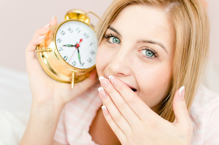 sweet cute charming young woman blond girl with sleepy face and an alarm clock in hand photo