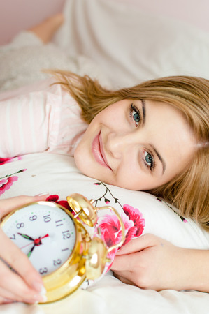 portrait of beautiful charming young woman blond girl happy smiling & looking at camera with an alarm clock in hand photo