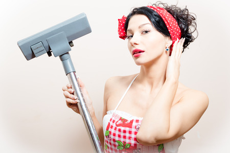 closeup portrait on funny charming young beautiful brunette woman pin-up girl with vacuum cleaner raised in hand straightens her hair