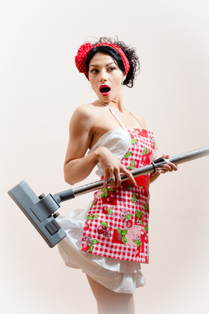 pretty housewifely attractive young woman sexually funny pin-up girl is surprised because the vacuum cleaner eats her dress portrait photo