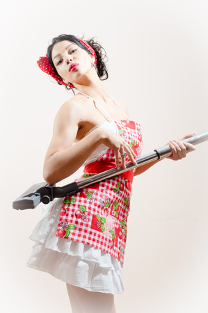 beautiful funny young brunette pinup woman embracing vacuum cleaner photo