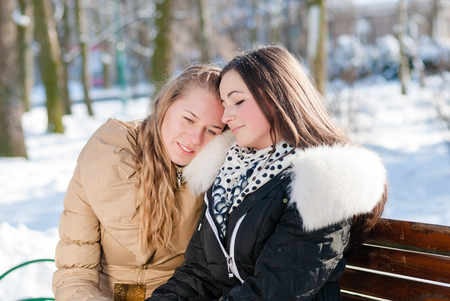 two happy attractive charming girls sitting on a bench in winter where one of them leaned on the shoulder of another portrait photo