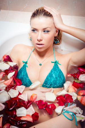 spa treatment closeup portrait: glamour beautiful seductive girl in turquoise swimsuit with makeup lying in the bath with rose petals photo