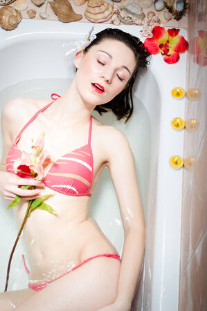 gorgeous sweet charming young woman with red lips holding lily flower in hands relaxing in the bath  photo