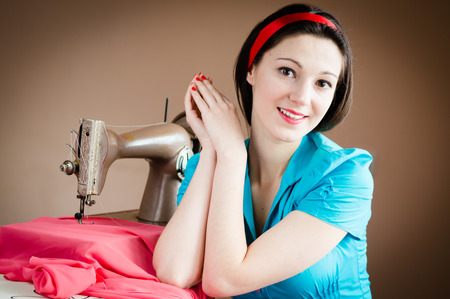 needlewoman: closeup portrait of attractive nice beautiful young pinup style woman in blue shirt smiling and sewing machine happy smiling & looking at camera