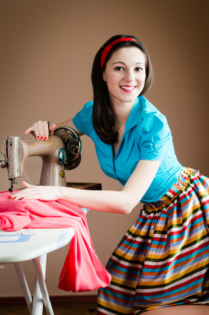 needlewoman: beautiful young nice pinup woman in blue shirt with hands on sewing machine & red fabric happy smiling looking at camera on brown background