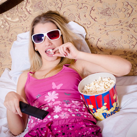 cute young blond woman in color pajamas lying in bed with TV remote control in hand watching movie in 3D glasses and eating popcorn photo