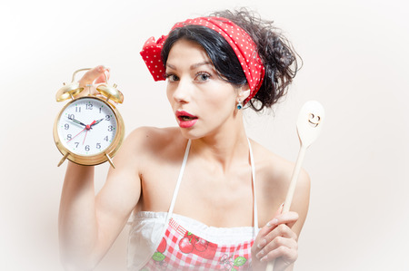 portrait of funny beautiful brunette woman pinup girl wearing apron holding alarm clock and spoon in hand, looking at camera on white background photo
