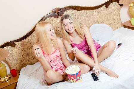 movie at home: 2 adorable attractive pretty young blond women having fun sitting in bed with popcorn, watching TV and happy smiling, laughing