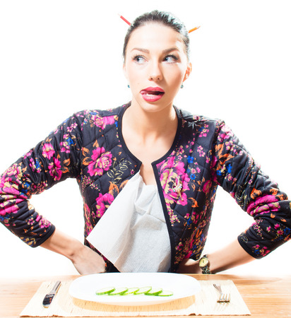 indecision: attractive beautiful brunette young woman licks lips, plate with chopped cucumber in front of her isolated portrait Stock Photo