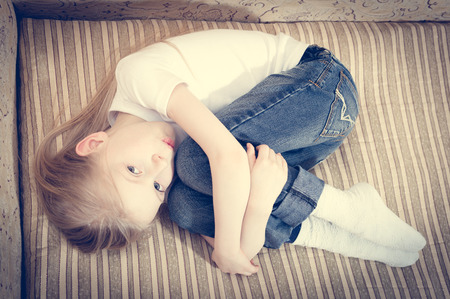 Beautiful child blond girl lying on the sofa hugging knees & looking at camera