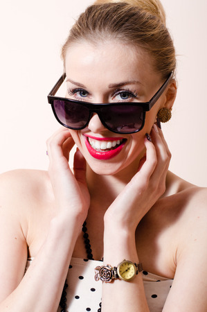 Beautiful blond pinup woman with sunglasses happy smiling & looking at camera on white background portrait photo