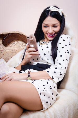 Beautiful pinup woman looking happy smiling with mobile phone photo