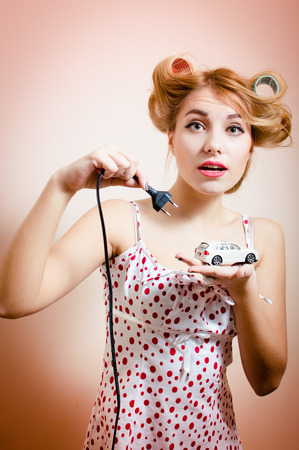 Beautiful blond elegant young pinup woman plugging for charging model toy car with electric cord looking at camera portrait photo