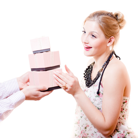 sincere: Beautiful sweet, sincere, gentle blond young woman received wonderful gifts in pink boxes from mans hands & happy smiling on white background Stock Photo