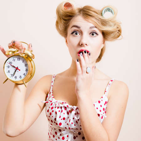 closeup portrait of surprised young beautiful green eyes woman attractive funny blond pinup girl holding golden alarm clock and looking at camera on light background photo