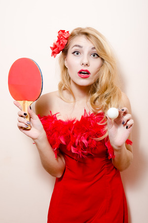 portrait of elegant beautiful glamour girl attractive young blond pinup woman dazedly in red dress with flower in hair and bat ball for table tennis on white background photo